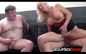 Busty mature lady sucking and fucking with two guys